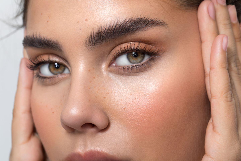 Frau mit grünen Augen schaut mit ausdrucksstarkem Blick in die Kamera