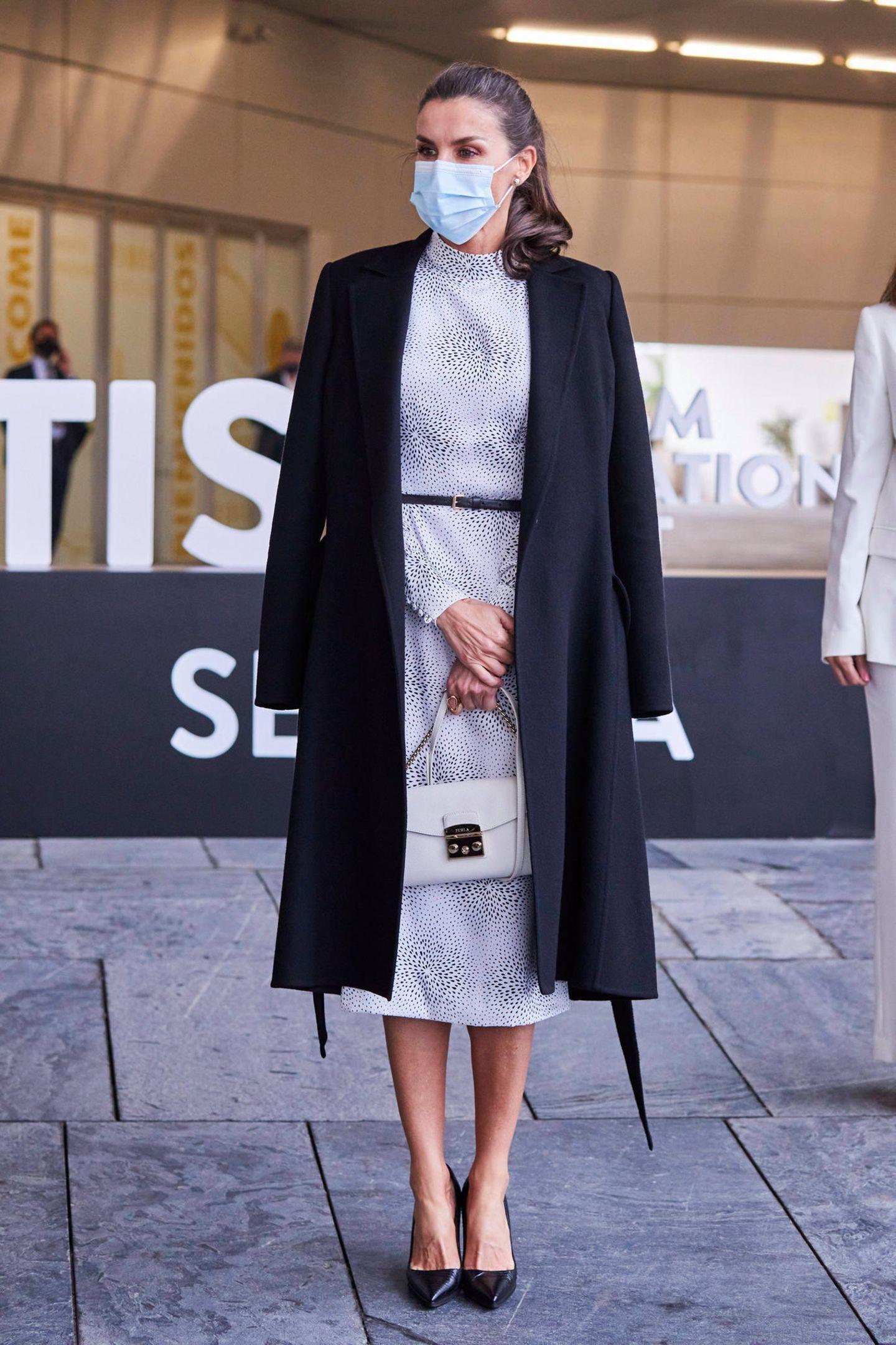 """Zur feierlichen Eröffnung des Tourism-Innovation-Gipfels in Sevilla wähltKönigin Letizia einen Look der Extraklasse – nicht zuletzt wegen eines simplen, aber genialen Fashion-Tricks. Zum gemusterten Kleid von Cherubina (280 Euro) trägt die Monarchin einen schwarzen Wollmantel, den sie sich locker über die Schultern legt. Der Clou: Dadurch entsteht eine Art optische Täuschung, die die Trägerin noch schlanker wirken lässt. Den Look komplettieren schwarze Pumps und eine weiße Handtasche von Furla (um 300 Euro).  Es ist übrigens nicht das erste Mal, dass wir Letizia in dem Kleid von Cherubina sehen. Bereits 2019 wählte sie am """"Garter Day"""" in Windsor das gemusterte Dress."""