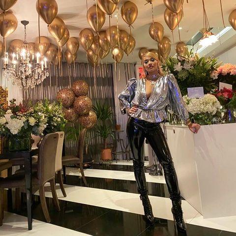 Pompös, extravagant und ein bisschen dekadent feierte Rita Ora am Wochenende ihren 30. Geburtstag. Doch trotz unzähliger Luftballons, riesiger Blumensträuße und einer mehrstöckigen Geburtstagstorte können wir unseren Blick einfach nicht von ihrem Wow-Dekolleté abwenden. Die Sängerin lässt in einem Silber-Metallic-Oberteil tief blicken und kombiniert zur Bluse eine schwarze Lack-Leggings. Und als wäre das nicht schon genug, setzt Ritaauch in Sachen Make-up mit einemXXL-Cat-Eye-Lidstrichvoll und ganzauf Extravaganz.
