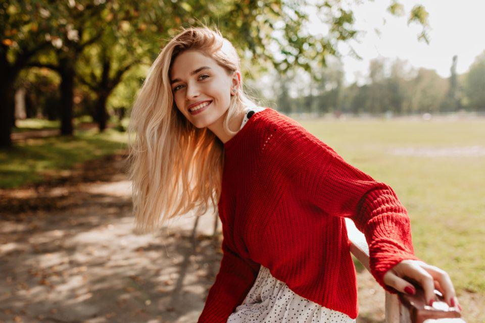 Resilienz stärken: Lächelnde blonde Frau mit rotem Pullover.