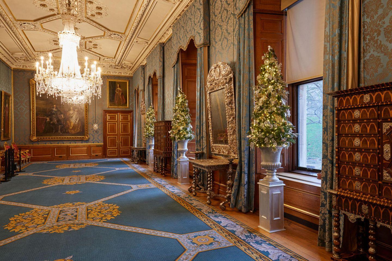 Statt eines großen XXL-Baumes wurden auf diesem Flur drei schmale, kleine Bäume reich geschmücktund auf Säulen dekoriert.