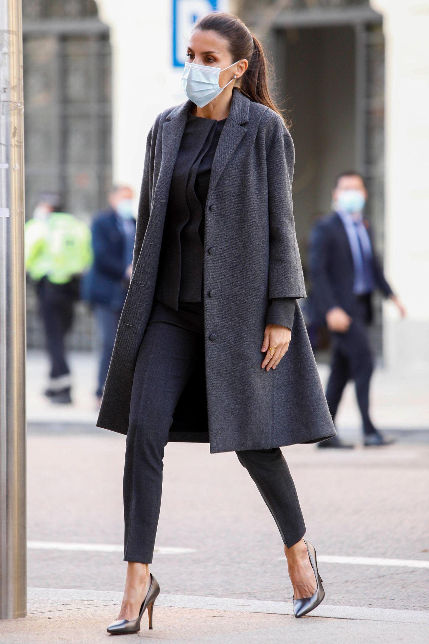 """Königin Letizia gehört zu den stilsichersten Royals überhaupt. Kein Wunder, dass sie auch in diesem schlichten grauen Lookbei einer Arbeitssitzung der Stiftung der spanischen Sprache """"FundéuRAE"""" in Madrid einfach bezaubernd aussieht. Die trägt eine elegante Kombi aus Blazer und Hose von HUGO BOSS (rund 660 Euro), metallische Pumps von Magrit (rund 300 Euro) und einen Tweed Mantel von Nina Ricci (etwa 2200 Euro). Den Mantel trägt Letizia allerdings schon seit mehr als fünf Jahren – der muss definitiv ein Lieblingsstück der Königin sein."""