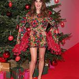 SchauspielerinNatalia Avelon sieht beinahe aus wie eine Weihnachtskugel! Der rote Jumpsuit mit goldenen, grünen und Blauen Farbakzenten schreit geradezu nach Weihnachten. Die Trompetenärmel mit Troddeln sind das Tüpfelchen auf dem i. Gewagt, aber echt cool!