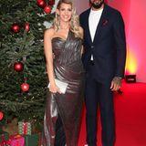 Ein Dreamteam auf allen Ebenen: Sarah und Dominic Harrison strahlen auf dem Red Carpet. Besonders elegant ist natürlich das bodenlange Kleid von Sarah, dass durch die dezenten Raffungen und den Herzausschnitt eine richtig tolle Figur macht.