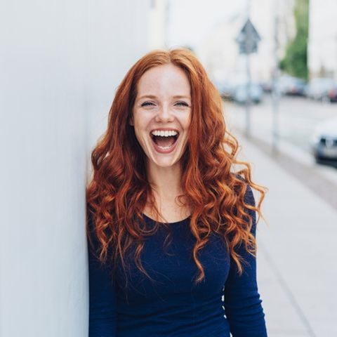 Aszendent Widder: Rothaarige lächelnde Frau.