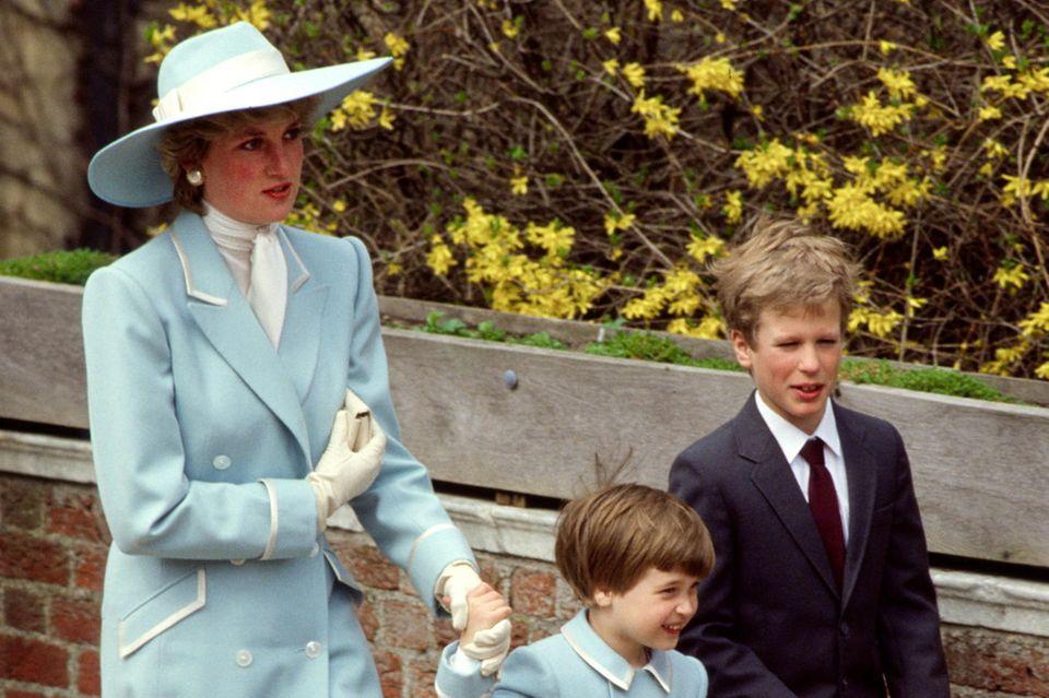 Hach, wir lieben diese Retro-Bilder und schwelgen in Erinnerungen! Hier ist Prinzessin Diana (†) 1987 mit dem kleinen Prinz William und ihrem Neffen Peter Phillips unterwegs zum Oster-Gottesdienst. Diana trägt einen blass-blauen Mantel mit doppelter Knopfleiste und weißen Applikationen von Catherine Walker - William trägt eine Mini-Version davon.