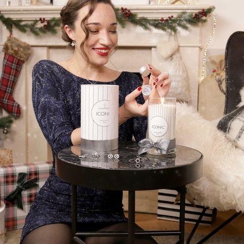 Frau mit weihnachtlichen Hintergrund hält Schmuckstück aus der Juwelkerze in der Hand