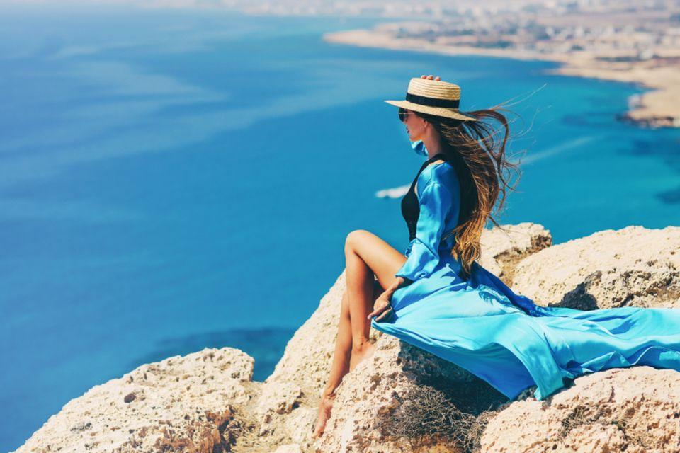 Aszendent Skorpion: Sitzende Frau im blauen Kleid blickt aufs Meer.