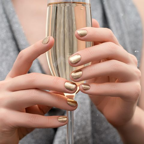 Silvester-Nägel: Frau mit goldenem Nagellack hält ein Glas Sekt in den Händen