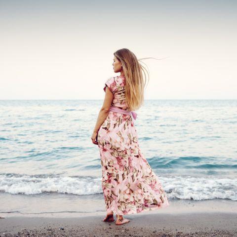 Aszendent Krebs: Frau im langen Kleid steht am Wasser.