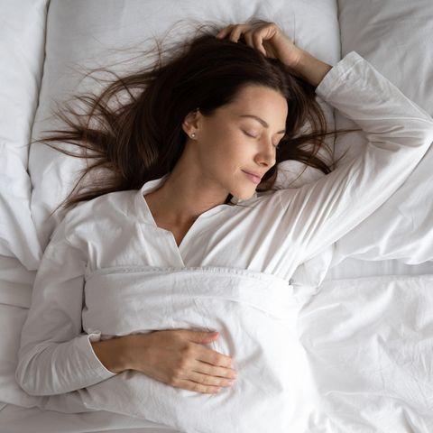 Frau mit langen braunen Haaren liegt im Bett und schläft