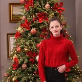 """In der Vorweihnachtszeit besucht Mackenzie Foy das """"Hallmark Channels Home & Family""""- Event in den Universal Studios in Kalifornien. In einem weihnachtsroten Strickpulli posiert die Schauspielerin vor einem üppig geschmückten Tannenbaum."""