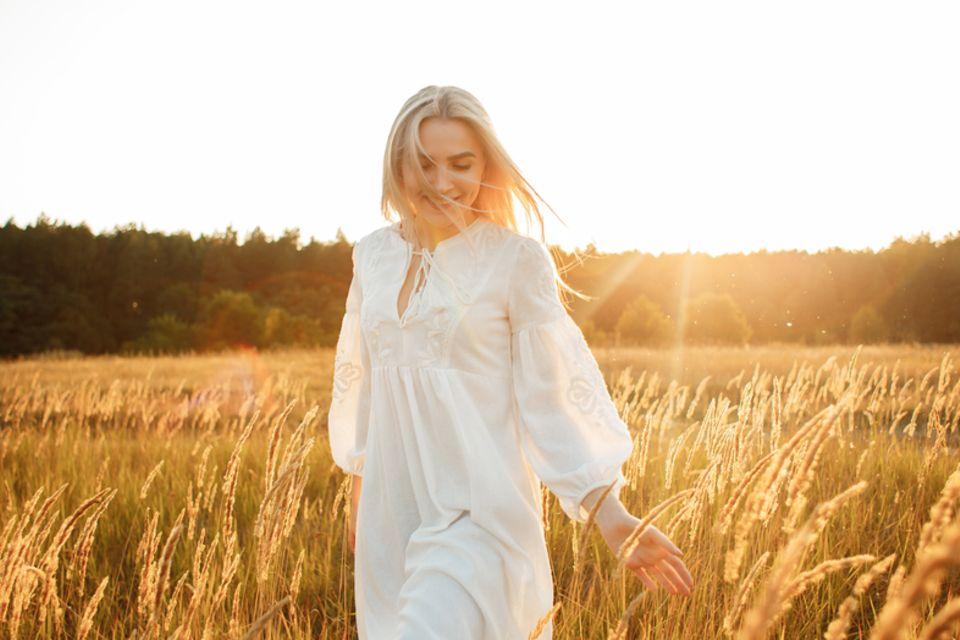 Aszendent Stier: Blonde Frau im weißen Kleid geht durch ein Weizenfeld.