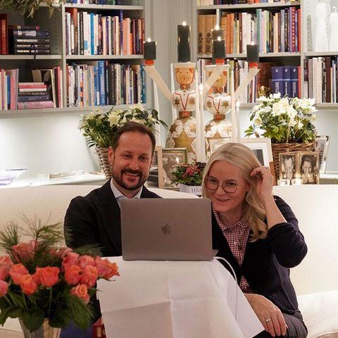 Für ein virtuelles Treffen mit einem sozial engagierten Rentner-Ehepaar haben sich Prinz Haakon und Prinzessin Mette-Marit kurzerhand eine kleine Büroecke in ihrer gemütlichen Bibliothek eingerichtet. Im Hintergrund ist bereits alles weihnachtlich dekoriert, Kerzen leuchten und überall stehen frische Blumen. So lässt es sich doch arbeiten!