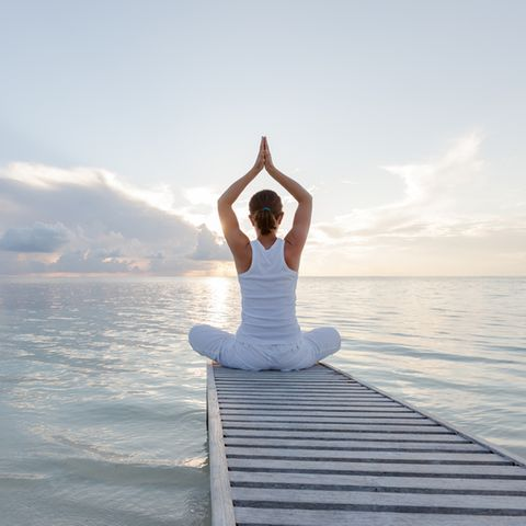 Aszendent Waage: Frau in Yoga-Pose am Meer.
