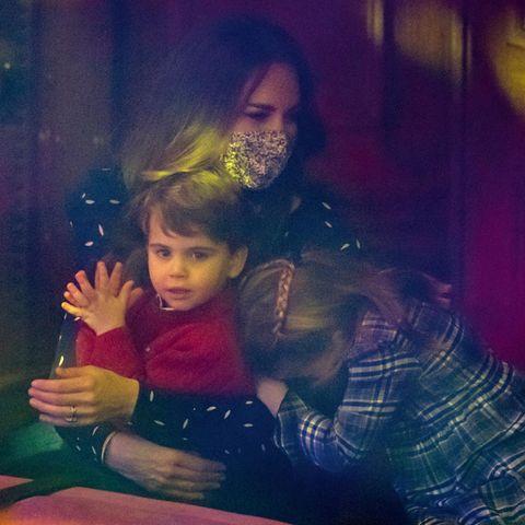 Prinzessin Charlotte wird langsam etwas müde und kuschelt sich kurz an Mamas Arm. Dafür ist Prinz Louis nun hellwach und klatscht den Mimen auf der Bühne Beifall.