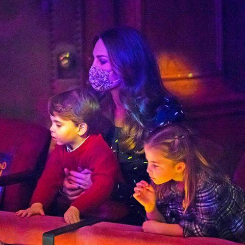 """Royals auf dem roten Teppich: Prinz Louis, Herzogin Catherine und Prinzessin Charlotte verfolgen gebannt das Pantomimen-Stück """"Pantoland""""."""
