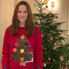 Was für ein schönes Weihnachtsfoto: Pippa Middleton gewährt uns nicht nur einen Blick auf ihren bereits geschmücktenTannenbaum, sondern auch sonst scheint die Schwester von Herzogin Kate vollends in Weihnachtsstimmung zu sein. In einem roten Pullover mit aufgedruckten Weihnachtsbaum versprüht sie auf Anhieb gute Laune. Und was wir zur Veröffentlichung des Bildes noch nicht wussten: Unter dem Tannenbaummotiv ihres Pullis versteckt sich eine kleine Babykugel. Die 37-Jährige erwartet ihr zweites Kind. Was für eine süße Weihnachtsüberraschung!