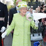 Als Vorlage diente dem Unternehmen wohl dieses Foto, auf dem die Queen in einem grünen Mantel, weißen Handschuhen und einer schwarzen Tasche zu sehen ist und Blumen anlässlich ihres 90. Geburtstags aus der Menschenmenge entgegen nimmt.