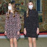 """ZurKuratoriumssitzung der """"Prinzessin von Girona""""-Stiftung in Madrid erscheinen Prinzessin Leonor (links) und Prinzessin Sofia (rechts) in zwei hübschen Kleidern, die sich zwar vom Schnitt ähneln, doch im Design unterschiedlicher nicht sein könnten. Wohingegen Sofia auf ein Polka-Dot-Kleid von Zara in Schwarz-Weiß setzt, bringt Leonor durch ihr fliederfarbenes Seidenkleid des Labels Maksu Roma Farbe ins Spiel. In der Schuhwahl sind sich die Schwestern allerdings einig: Sie setzen beide auf schwarze, schlichte Ballerinas, die ihren hübschen Look gekonnt abrunden."""