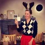 """Vor dem flackernden Kamin genießt Elizabeth Banks eine Tasse Eierlikör mit einem SchussRum und wünscht mit Rentiergeweih auf dem Kopf ihren Fans bei Instagram ein """"Happy Hanukkah""""."""