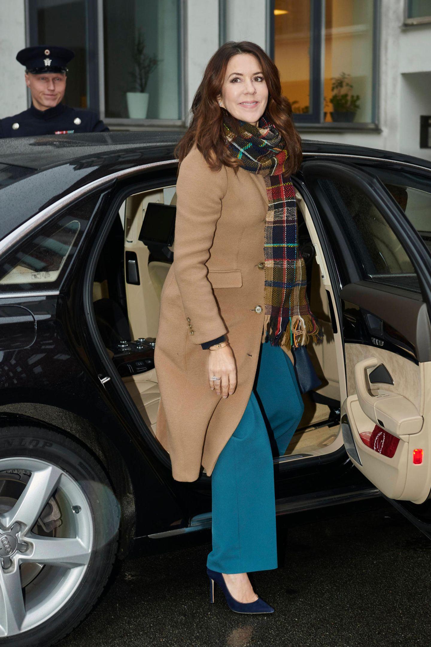 """Grauer Winter? Nicht bei Prinzessin Mary! Bei den Feierlichkeiten zum einjährigen Bestehen des """"Global Refugee Forum"""" zeigt sie sich in einem camelfarbenen Mantel, petrolblauer Hose und mit einem kariertem Schal, der alle Farben des Looks raffiniert aufgreift."""