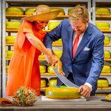 """Zu zweit müssen Königin Máxima und König Willem-Alexanderdas Käse-Wiegemesser ergreifen, um sich bei ihrem Besuchin der Käserei """"De Deelelen"""" im Örtchen Tijnjeeine dicke Scheibe von dem glänzenden Laib abzuschneiden."""