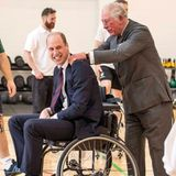 """Nach mehreren verpatztenWürfen beim Rollstuhl-Basketballs im """"Defence Medical Rehabilitation Centre Stanford Hall"""" schreitet Prinz Charles beherzt ein und schiebt seinen Sohn Prinz William näher an den Korb ran. Anschließend gibt es eine kleine Massage."""