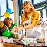 """Etwas skeptisch blicktKönigin Máxima drein, als sie kleinen Pfadfinderinnen im """"De Kookerij in Noordwijkerhout"""" anlässlich des 100-jährigen Bestehens der """"Welpen"""" (dt. Wölflinge) von Scouting Nederland beim Backen süßer Cupcakes hilft."""