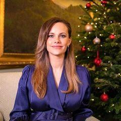 Prinzessin Sofia nimmt an einer Gala teil, die Alltagshelden ehrt. In einem dunkelblau glänzenden Kleid und mit elegant zur Seite gekämmten Haaren strahlt sie vor weihnachtlicher Kulisse. Dank derraffinierten Wickelfront und dem Gürtellässt sich ihr wachsender Babybauch im Sitzen gut verstecken und das Kleid wirkt nicht zu eng. Es stammt vom schwedischen Label ByMalina und kostet umgerechnet rund 345 Euro.