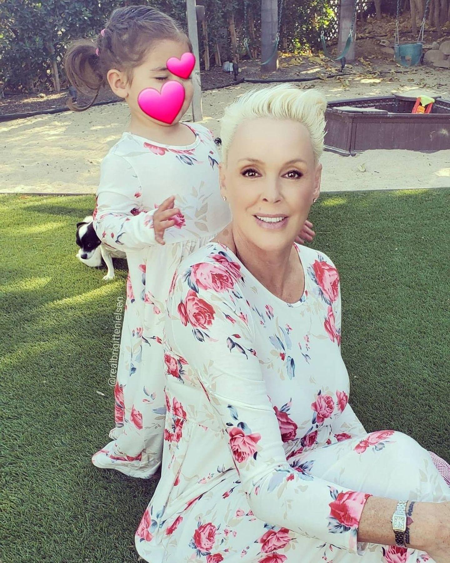 """""""In blumiger Stimmung"""" sind Brigitte Nielsen und ihre kleine Tochter, die sie liebevoll als Mini-Me bezeichnet: Beide tragen das gleiche Kleid mit floralem Muster und sehen darin zauberhaft aus"""