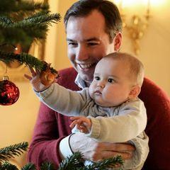 Neugierig erkundet der kleine Charles auf dem Arm von Papa Guillaume den interessanten Weihnachtsschmuck.