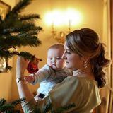 Die roten Weihnachtskugeln würde Baby Charles am liebsten selbst in die Hand nehmen, doch MamaStéphanie passt lieber ein bisschen dabei auf.