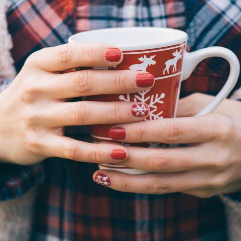Weihnachtsnägel: Frau mit rotem Nagellack und weißen Schneeflocken