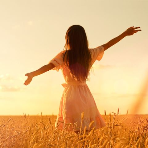 Feuerzeichen: Frau geht durch ein Weizenfeld.