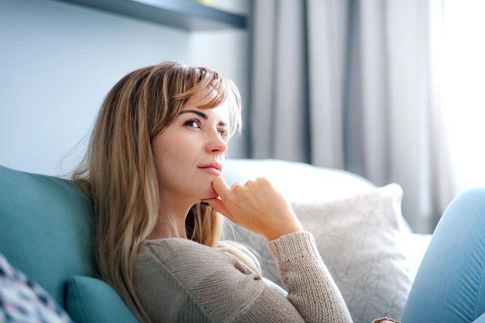 Deszendent: Frau sitzt auf der Couch und denkt nach.