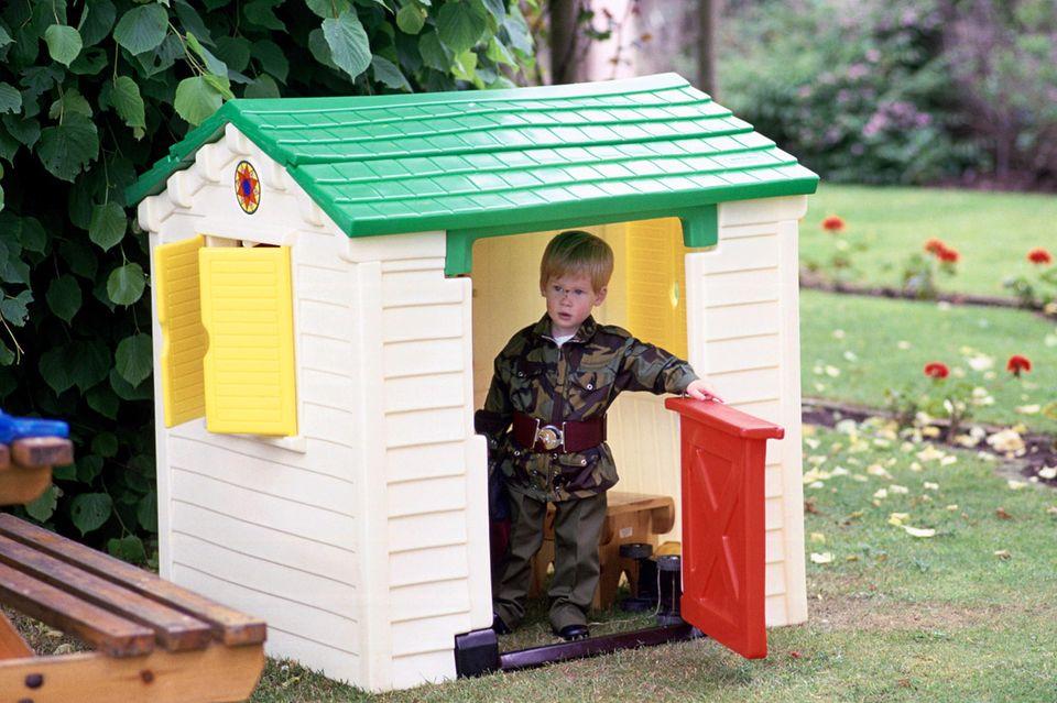 Prinz Harry, damals süße anderthalbJahre alt, in einem Spielzeughaus. Aufgenommen wurde das Foto auf dem Anwesen seines Vaters, Highgrove.
