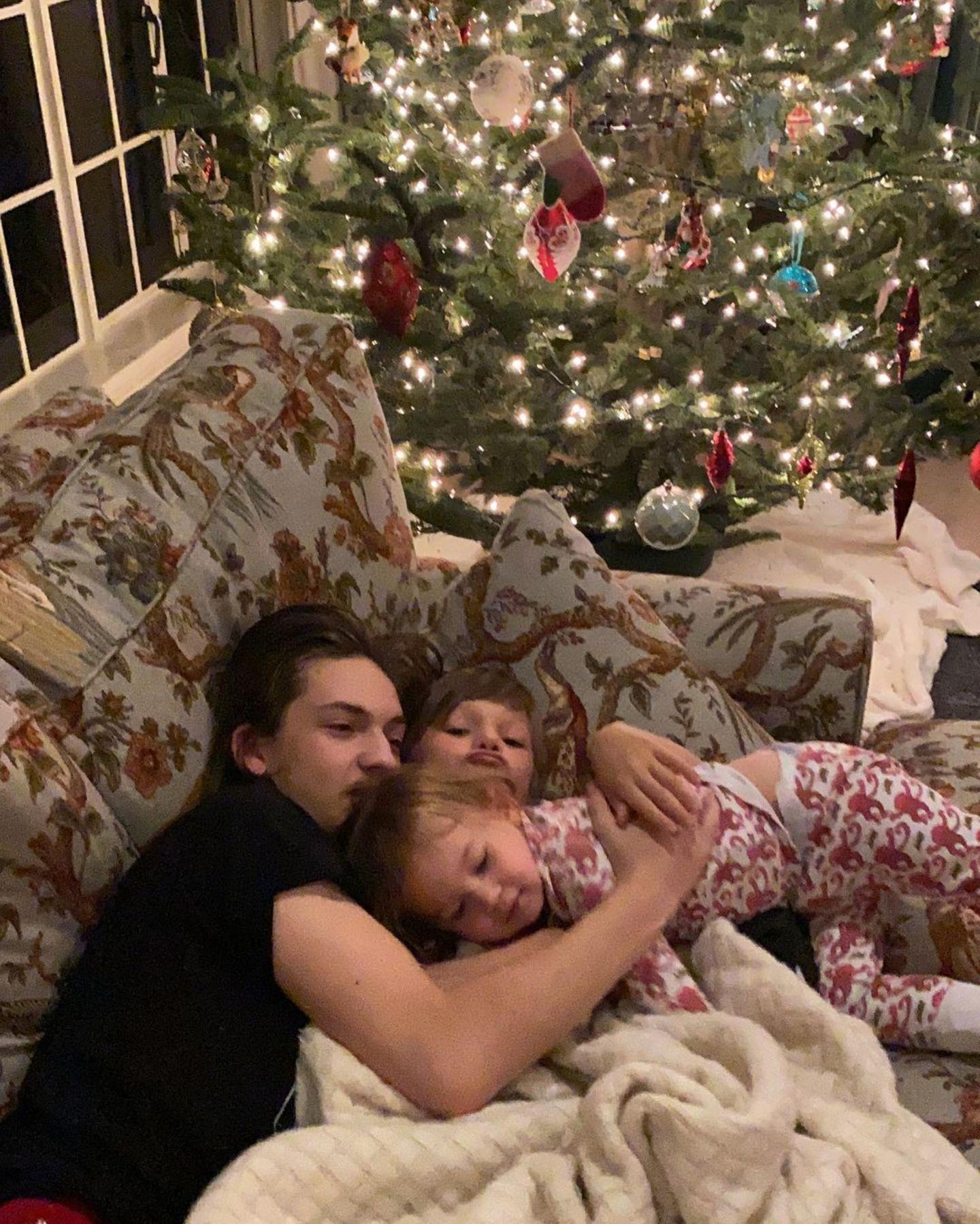 Stolz postet Kate Hudson ein Foto ihrer Kinder Ryder, Bingham und Rani, die eng aneinander gekuschelt auf dem Sofa vor dem geschmückten Weihnachtsbaum liegen.