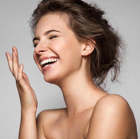 Lachende Frau mit hochgesteckten Haaren hält die Hand vor das Gesicht