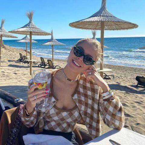 Victoria Swarovski fühlt sich in der Modewelt zu Hause, weshalb sie sich auch an verstaubte Mode-Klassiker wie das Twin-Set ran traut. Mit coolen Accessoires peppt sie die braunbeigeZwillings-Kombi auf. Besonderes Highlight sind die zahlreichen Ringe, die mit großen Steinen verziert sind.