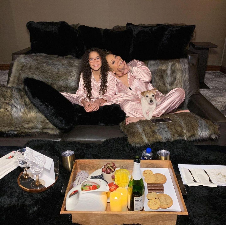 """Superdiva Mariah Carey und Töchterchen Monroe genießen einen entspannten Filmabend auf der Couch. Passende Seidenpyjamas in Rosa dürfen dabei natürlich nicht fehlen – schließlich schauen die beiden """"Girls Club""""."""