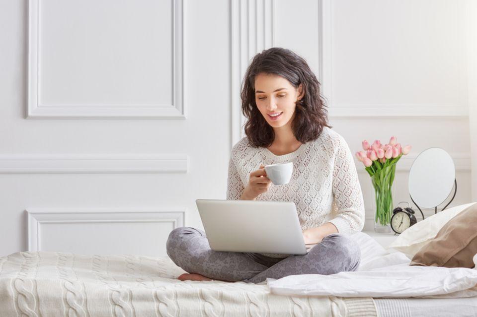 ALPEN-Methode: Frau sitzt auf dem Bett und arbeitet am Laptop.