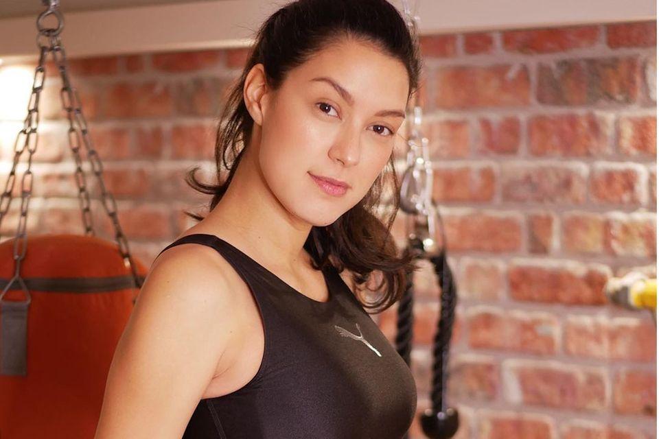 Rebecca Mir hält sich auch während der Schwangerschaft fit und zeigt sich in einem schwarzen Zweiteiler von Puma, der ihren wachsenden Babybauch toll in Szene setzt.
