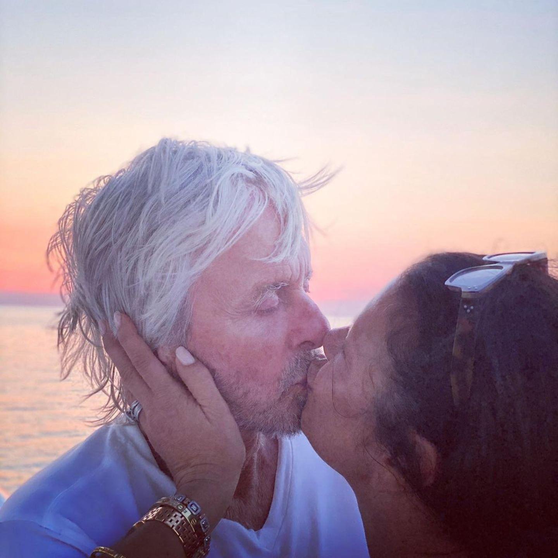 """Ein Kuss und ein Shakespeare-Zitat besiegeln ihre Liebe: """"Ich kann kein freundlicheres Zeichen der Liebe ausdrücken, als diesen freundlichen Kuss"""", schreibt Catherine Zeta-Jones zu diesem seltenen Kuss-Foto mit Mann Michael Douglas in romantischer Stimmung am Strand."""