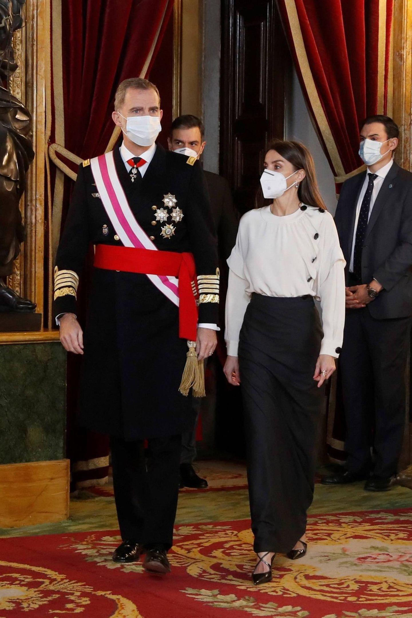 Beim Neujahrsgruß an das Militär setzt Königin Letizia dieses Jahr auf einen ganz neuen Look. In den vergangenen Jahren war ein langes festliches Kleid fast obligatorisch, meistin einem Blauton. Doch dieses Jahr überrascht die Frau von König Felipe in einer Rock-Blusen-Kombi, die zudem recht schlicht ausfällt. Wie bereits bei ihren letzten Outfits versucht Königin Letizia vorrangig auf spanische Labels zurückzugreifen oder recycelt alte Lieblingsteile, um sich solidarisch mit dem wirtschaftlich angeschlagenen Volk zu zeigen. Die Bluse ist von Maksu und die Schuhe von Magrit.