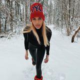 ModelDarya Strelnikova nutzt den verschneiten Wald als Kulisse, um ihr Outfit zu präsentieren.