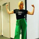 """Ruth Moschners Look fällt nicht nur dank grüner Marlene Hose auf. Vor allem ihr Shirt sticht ins Auge:Die Message """"Fight Like A Girl"""" (dt. Kämpfe wie ein Mädchen) ziert ihr schwarzes Oberteil. Eindeutig zweideutig! Während """"Du kämpfst wie ein Mädchen"""" vor einigen Jahren noch abwertend gemeint war, lassen sich die Frauen von heute davon nicht mehr beirren. Denn die können erst recht kämpfen - das beweisen nicht nur Ruths Armmuskeln!"""