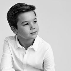 Auch ihr Zwillingsbruder Vincent ist ganz schön groß geworden: In einem weißen Hemd nimmt er eine lässige Pose ein. An seinem Handgelenk ist ein filigranes Lederarmband zu erkennen, die Haare hat er cool nach hinten gekämmt.