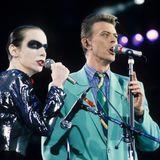 """Mit dem Tod von Freddie Mercury im November 1991 konnte David Bowie eines der größten Duette der Musikgeschichte , """"Under Pressure"""" nicht mehr """"richtig"""" performen. Bei einem Konzert zu Ehren des verstorbenen Queen-Frontmanns im April 1992 übernimmt Annie Lennox dessen Part. Bowies Signature-Look der damaligen Jahre waren, wie hier, farbenfrohe Anzüge."""