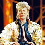 """In den 1980ern wird es für David Bowie nicht nur musikalisch richtig poppig, """"Let's Dance"""" ist bis heute einer seiner erfolgreichsten Hits, auch der Look ist unübersehbar Achtziger! Hier performt er während seiner """"Glass Spiders""""-Tour im Londoner Wembley Stadium."""
